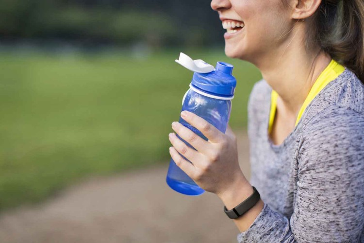 Jogger with fitbit drinking water