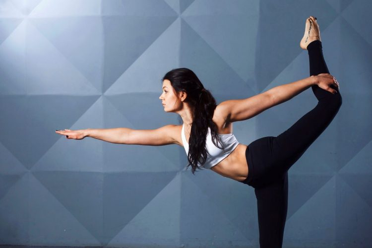 woman holds leg in yoga pose